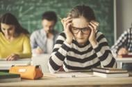 Students solving problem quiz in classroom behind blackboard